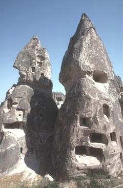 A üçhisar, dans la Cappadoce turque, des cheminées de fées, formées de cendres volcaniques soudées puis sculptées par l'érosion, ont été creusées en habitats troglodytes.