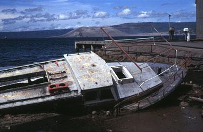 Lors de l'éruption du Tavurvur en Papouasie - Nouvelle-Guinée, en 1994, ce bateau s'est retrouvé échoué sur la côte par un raz-de-marée. On voit le volcan Vulcan assoupi en arrière-plan.