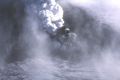 Éruption sous le glacier Vatnajökull en Islande le 9 octobre 1996. Une importante fissure, de 3 km de long et de 300 m de large, s'est ouverte. Un panache de cendres noires, éjectées à grande vitesse, côtoie un nuage blanc de vapeur d'eau.