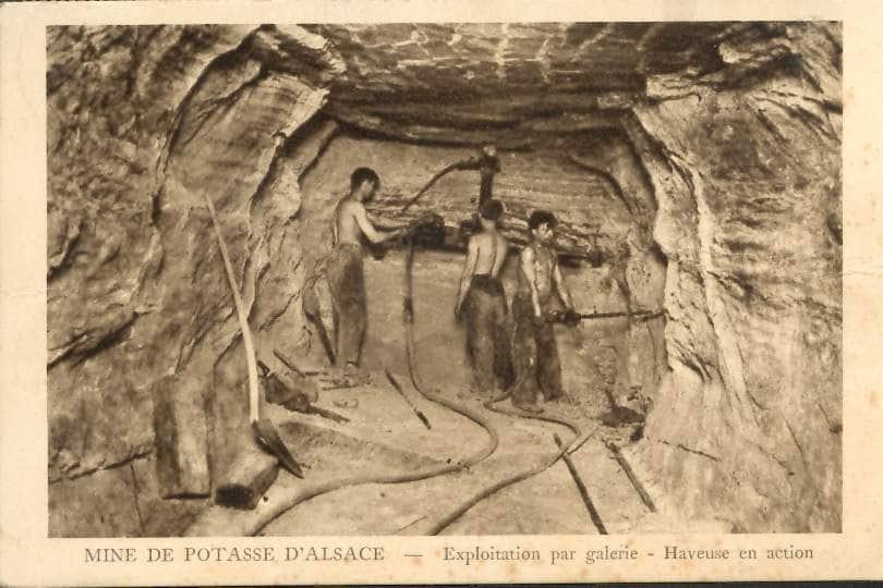 """Carte Postale Ancienne (CPA) : """"Mine de Potasse d'Alsace, haveuse en action"""", scène avec des mineurs."""