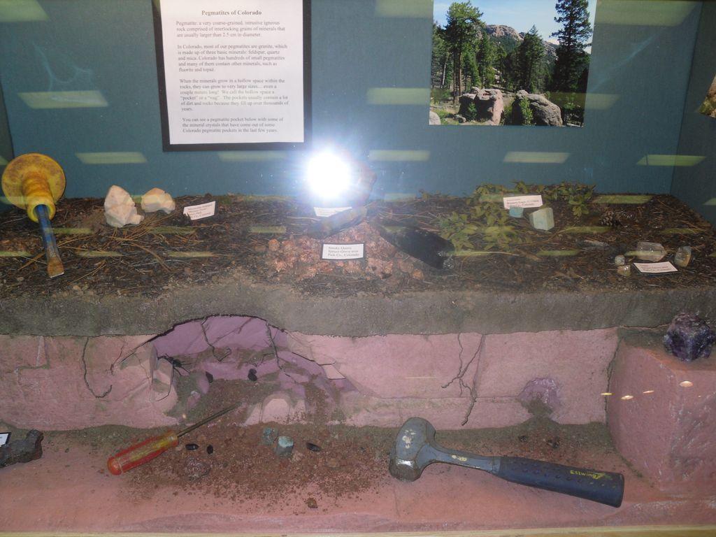 Vitrine montrant les minéraux dans leur milieu naturel et expliquant la collecte des minéraux.